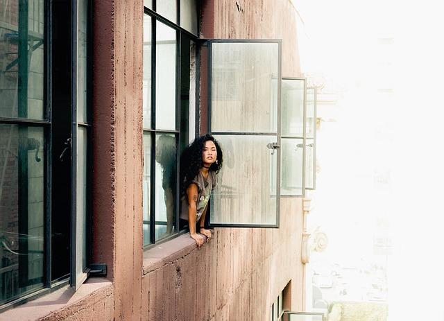 Činžiak, mladá žena pozerá z otvoreného okna.jpg
