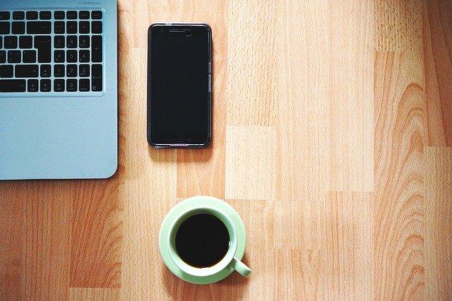 Drevený stôl, notebook, mobil a hrnček s kávou