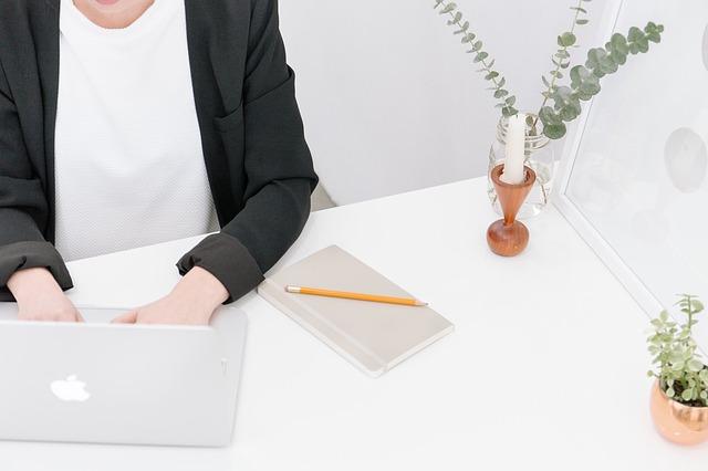 Žena v bielom svetri a čiernom saku píše na notebooku